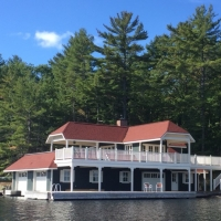 Muskoka Lakefront Cottage -  Boat dock with two-floored deck, two boat garages, lush pine trees in background