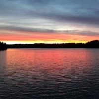 Muskoka waterfront - lake view photo - sunset with red sun rays reflecting over water horizon